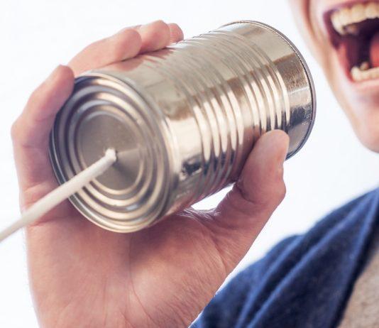 Hombre con jersey azul en la calle con una lata y una cuerda para comunicarse gritando