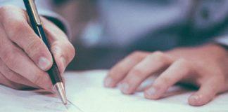 hombre con camisa en una oficina sentado en un escritorio firmando un documento