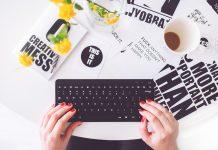 Teclado con manos de mujer y palabras de fondo en un escritorio