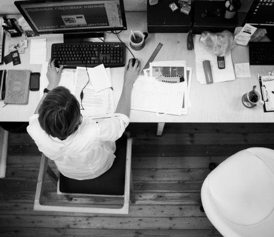 hombre con camisa blanca en una oficina blanca trabajando con el ordenador