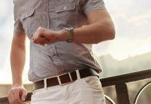 hombre con camisa beige en un puente de madera mirando su reloj de pulsera