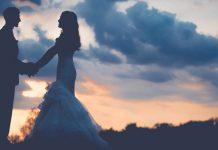 hombre y mujer con trajes de boda en un campo atardeciendo cogiendose de las manos mirandose