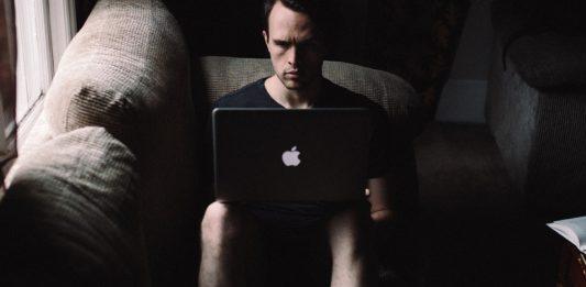 hombre serio en una casa sentado en el sofa mirando el ordenador portatil