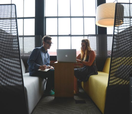 personas jovenes en una oficina sentados en dos sofas amarillo y gris trabajando con el ordenador