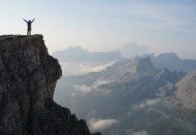 persona con una mochila en la cima de una montaña levantando los brazos mirando las montañas