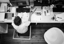 hombre con camisa sentado en una oficina visto desde arriba trabajando con el ordenador