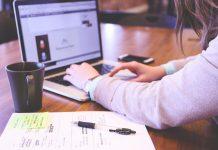 mujer trabajando con el ordenador libreta y taza de cafe en la oficina