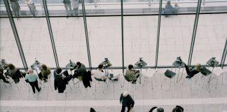 gente almorzando en una cafeteria con grandes ventanales