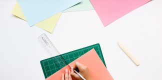 Manos en una mesa de una oficina con una cartulina regla y lapiz dibujando
