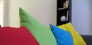 cojines de colores rojo verde azul y amarillo en un sofá oscuro