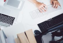manos de una persona en una oficina con varios ordenadores tecleando en un teclado blanco